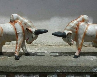 A pair of 1950's hand painted unfired clay temple toys in the form of fighting bulls.