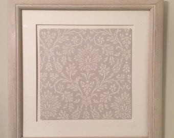 French country interior-shabby chic wooden frame filled with vintage fabric.