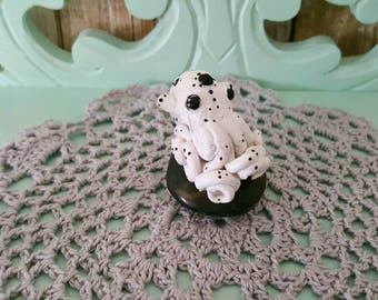 Polymer clay sculpted octopus on a black agate palm stone stand