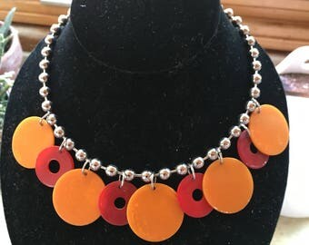 Necklace of orange and red bakelite circles on a ball chain