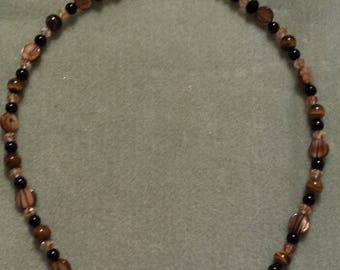 Brown wooden beads offset with black pearls and Swarovski Crystals intermixed