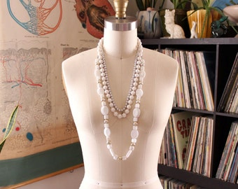 collection of vintage bead strand necklaces . white beads, flattened beads, plastic faceted, silver gray pearls
