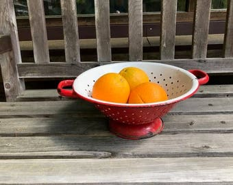 vintage red enamel colander use as a fruit bowl  fill with plants fill with ornaments