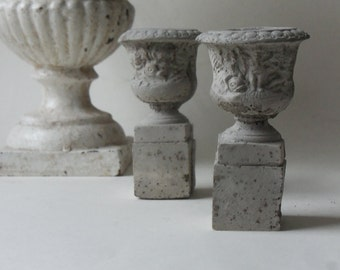 two mini cement urns