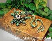Green sad little dragon on map book
