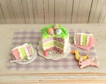 Miniature Easter Cake With Easter Eggs On Top, 2 Slices Of Cake, And 2 Easter Cookies