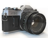 Legendary Most Popular  Camera 70s-80s CANON AE1 with FD 50mm/1.8 Normal Lens. Fully Working Condition. Normal wear. NO Dents. Battery incl.