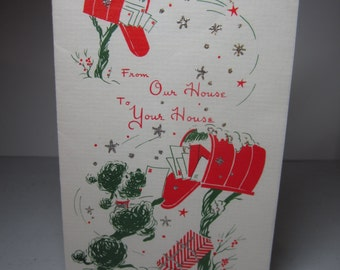 Colorful green and red mid century 1950's sunshine christmas card shows a poodle getting mail out of a mailbox in the snow silver glitter