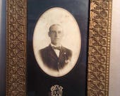 Antique fancy gilded picture frame with portrait photo
