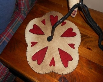 Candle mat, white primitive hearts in red stitched in the scallops.