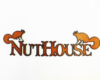 Nuthouse sign made out of rusted metal with images of squirrels