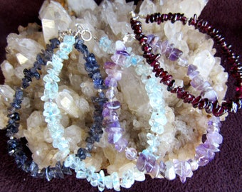 Bracelets  done in 4 different gemstone chip bracelets, iolite, blue topaz, amythest, garnet,  7inch in length, sterling silver clasps.
