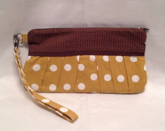 Wristlet/Clutch purse in a smart polkadot print with pleated front, zipper closure and detatchable hand strap