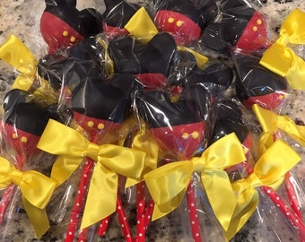 Mickey Mouse Cake Pops with yellow bows and paper straws