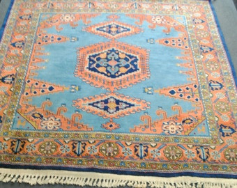 Persian rug made hands square blue and pink background
