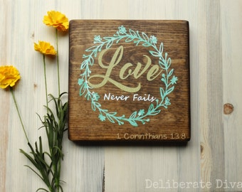 """7""""x7"""" Love never fails- Solid wood sign hand crafted and painted with 1 Corinthians 13:8 with gold lettering"""