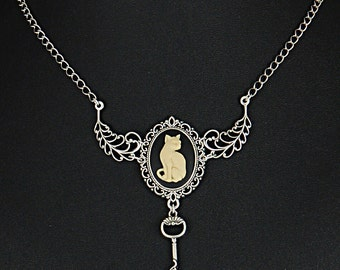 Lovely kitty cat cameo with filigree setting accented with a key with another kitty cat.