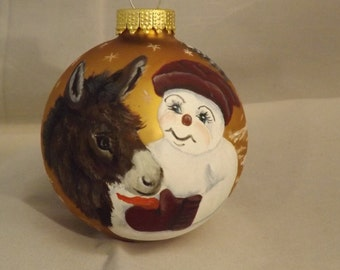 Donkey and Snowman painted on a gold ornament