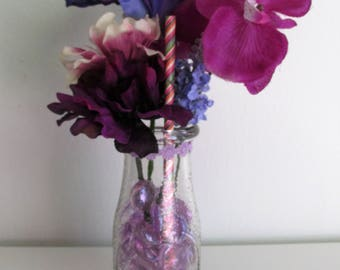 Purple Themed Silk Flower Arrangement in an Embossed Glass Milk Bottle with Glass Beads, featuring a Candy-Striped Pick
