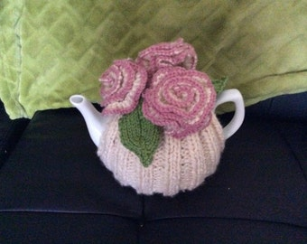 Hand knitted teacosy decorated with ivory roses with pink edging