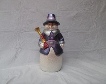 A ceramic bisque pilgrim snowman