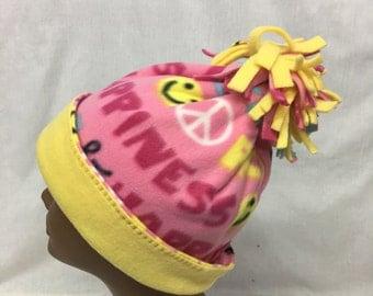 Colorful fleece cap with yellow fleece lineing trim around edge.