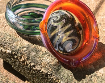 Glass ash tray with linework.