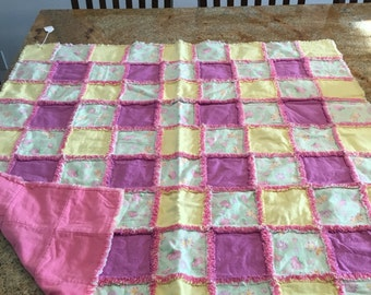 Pretty double flannel rag quilt, flowers, butterflies, pinks greens, and yellows.  Pink on back.  Warm, but lightweight. 38x38