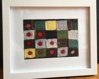 Knitted wool/cotton inchies with buttons in white wooden frame