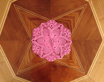 round doily in pink, in the form of the mandala