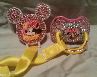 Mickey mouse pacifier with ribbon clip.