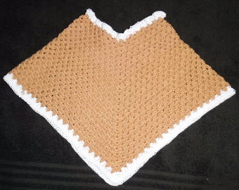A copper crochet Baby Poncho with white border.