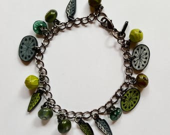 Green charm bracelet with glass beads and shrink plastic charms