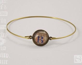 """Orbis"" - manuscript under glass bracelet"