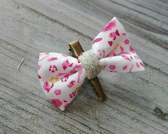 Fabric bow hair clip pink flowers on white background on bronze barrette