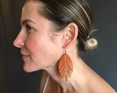 Orange leather metallic feather earrings