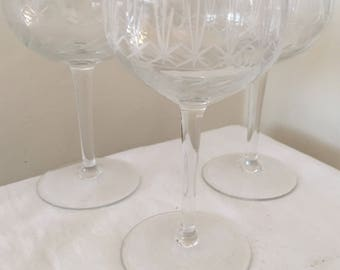 A set of three antique etched and cut wine glasses.