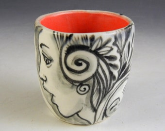 Black and white with red inside porcelain tea bowl story cup with faces