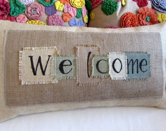 """The """"welcome"""" pillow natural burlap panel appliqued on blonde burlap . Approx. 13X25 lots of texture and dimension"""