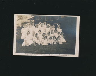 vintage postcard is a photo of schoolgirls in white dresses, 1900's