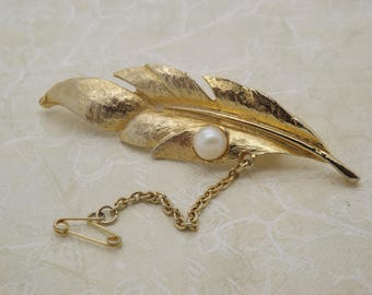 A fine vintage jewelry brooch made in a leaf design in patinated goldtone metal and set with a faux pearl. Also has safety chain