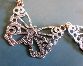 Flutterby Necklace is a trio of textured silver filigree butterflies captured by dainty goldfilled chain and a magnet clasp