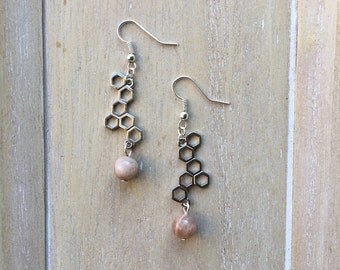 Silver colored dangle earrings with honeycomb pendant and sunstone bead