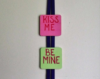 Hand-Painted Valentine's Day Candy themed Wall Hanger, featuring Kiss Me, Be Mine, and Love You, topped with a handmade bow