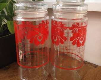 Two retro vintage glass storage canisters with red flower and grid design