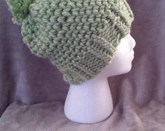 Sage green knit hat with pom pom.