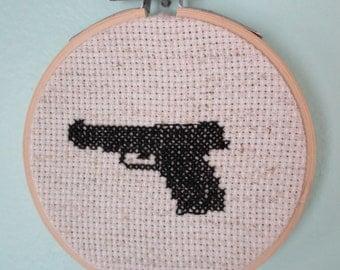 Miniature completed gun cross stitch in hoop