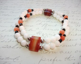 White coral stretch bracelet with orange quartz, cat eye glass beads and black firepolish beads