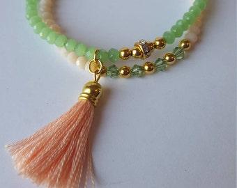 Bracelet pierres vert menthe et pêche pâle. Bracelet double. Pompon rose. Ajustable.