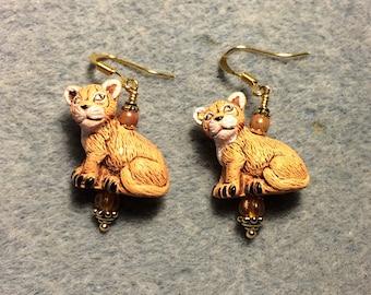 Orange ceramic lion cub bead earrings adorned with orange Czech glass beads.
